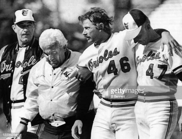 Pitcher Mike Flanagan of the Baltimore Orioles is helped off the field by manager Joe Altobelli trainer Ralph Salvone and Cal Ripken Sr #47 after...