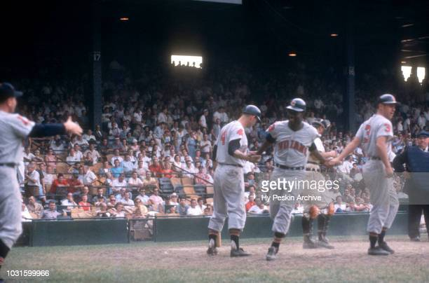 Pitcher Mudcat Grant of the Cleveland Indians is congratulated by teammates Woodie Held and George Strickland after hitting a threerun homerun during...