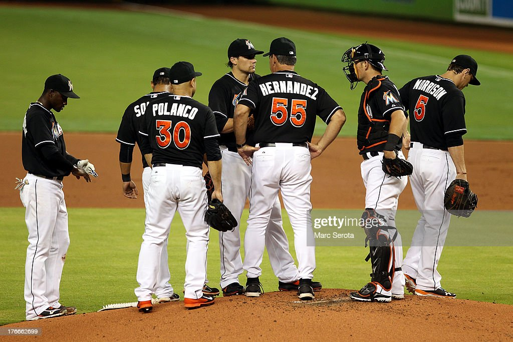 Pitcher Nathan Eovaldi #24 of the Miami Marlins chats with Pitching Coach Chuch Hernandez #55 and teammates against the San Francisco Giants at Marlins Park on August 16, 2013 in Miami, Florida. Eovaldi gave up 11 runs in three innings.
