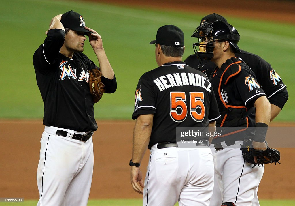Pitcher Nathan Eovaldi #24 of the Miami Marlins chats with Pitching Coach Chuch Hernandez #55 against the San Francisco Giants at Marlins Park on August 16, 2013 in Miami, Florida. Eovaldi gave up 11 runs in three innings.