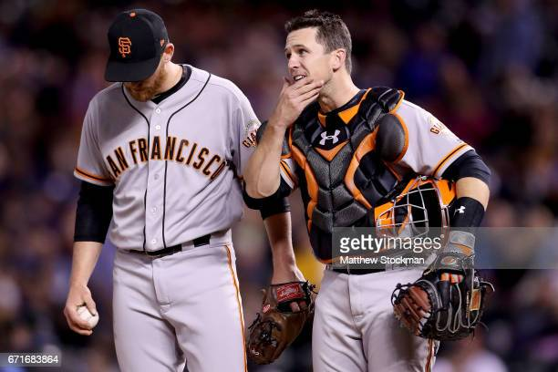Pitcher Neil Ramirez of the San Francisco Giants confers with catcher Buster Posey in the eighth inning against the Colorado Rockies at Coors Field...