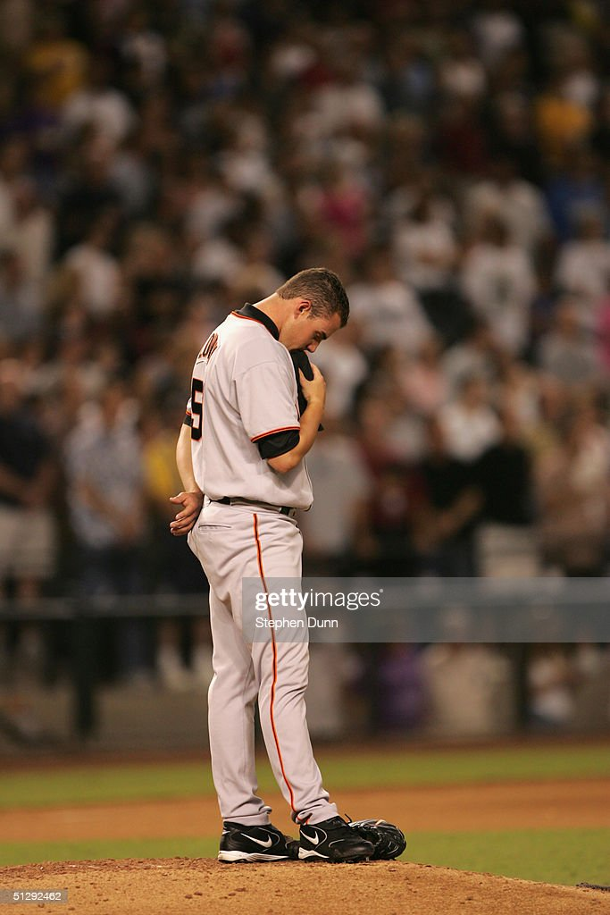 Pitcher Nick Lowry #51 of the San Francisco Giants stands as God Bless America is sung during the seventh inning stretch as a 9/11 tribute at the game between the Arizona Diamondbacks and the Giants on September 11, 2004 at Bank One Ballpark in Phoenix, Arizona.