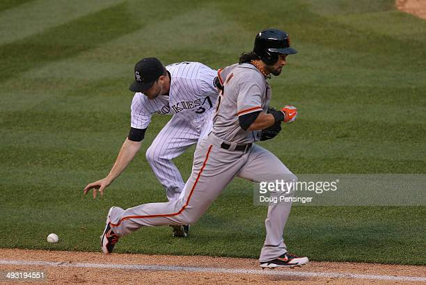 Pitcher Nick Masset of the Colorado Rockies can't handle a soft ground ball as Angel Pagan of the San Francisco Giants singles in the sixth inning at...