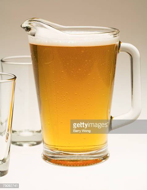 pitcher of beer and two empty glasses, close-up - pitcher stockfoto's en -beelden