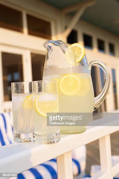 Pitcher of lemonade and glasses on railing