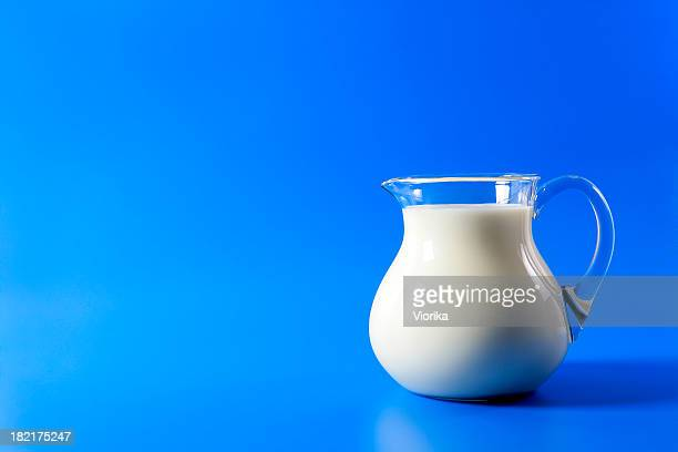 pitcher of milk on blue - pitcher stockfoto's en -beelden