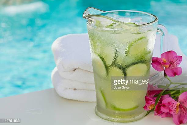 Pitcher of water with cucumber by pool