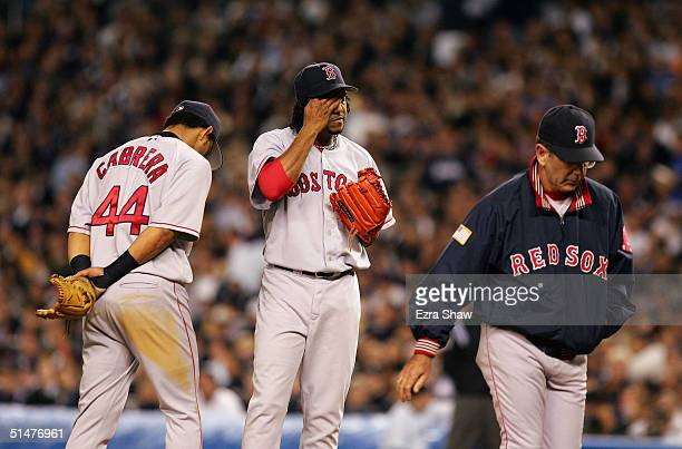 Pitcher Pedro Martinez of the Boston Red Sox reacts after a visit by pitching coach Dave Wallace and shortstop Orlando Cabrera in the forth inning...