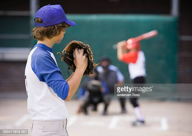 pitcher (13-15) preparing to throw baseball to batter - baseball pitcher stock pictures, royalty-free photos & images