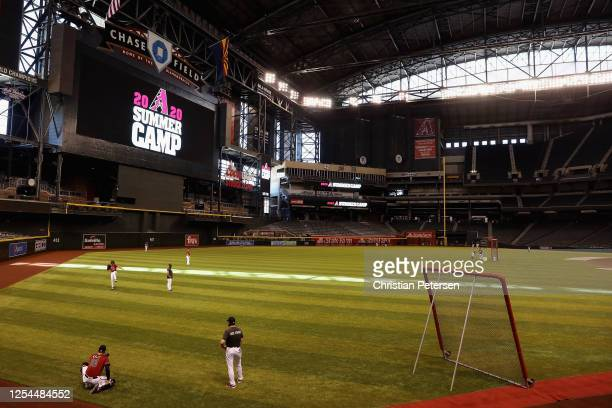 Pitcher Robbie Ray of the Arizona Diamondbacks warms up with catcher Carson Kelly as they participates in summer workouts ahead of the abbreviated...