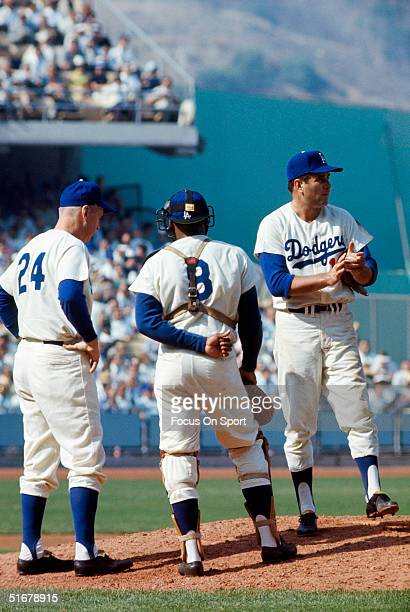 Pitcher Ron Perranoski looks toward the bullpen as Walter Alston and Catcher Johnny Roseboro look on during the World Series at Dodger Stadium on...