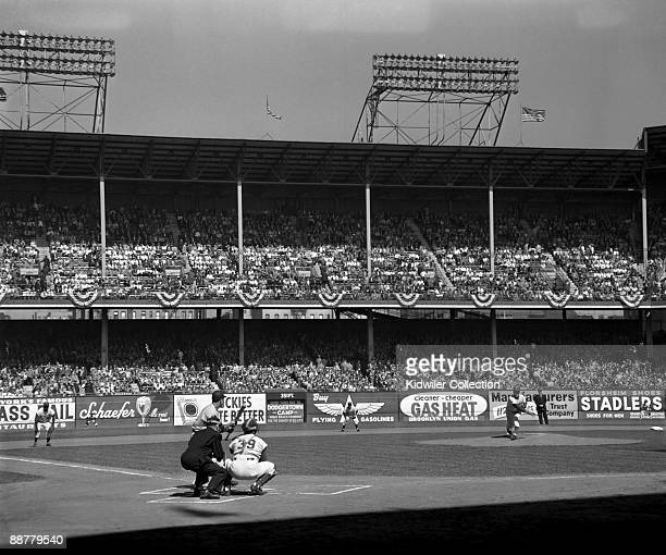 Pitcher Sal Maglie of the Brooklyn Dodgers throws a pitch as outfielder Hank Bauer of the New York Yankees squares to bunt during the top of the...