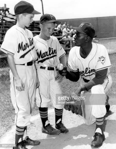 Pitcher Satchel Paige of the Miami Marlins of the International League shows the club's batboy Chet Fields and clubhouse boy Bobby Porter how to hold...