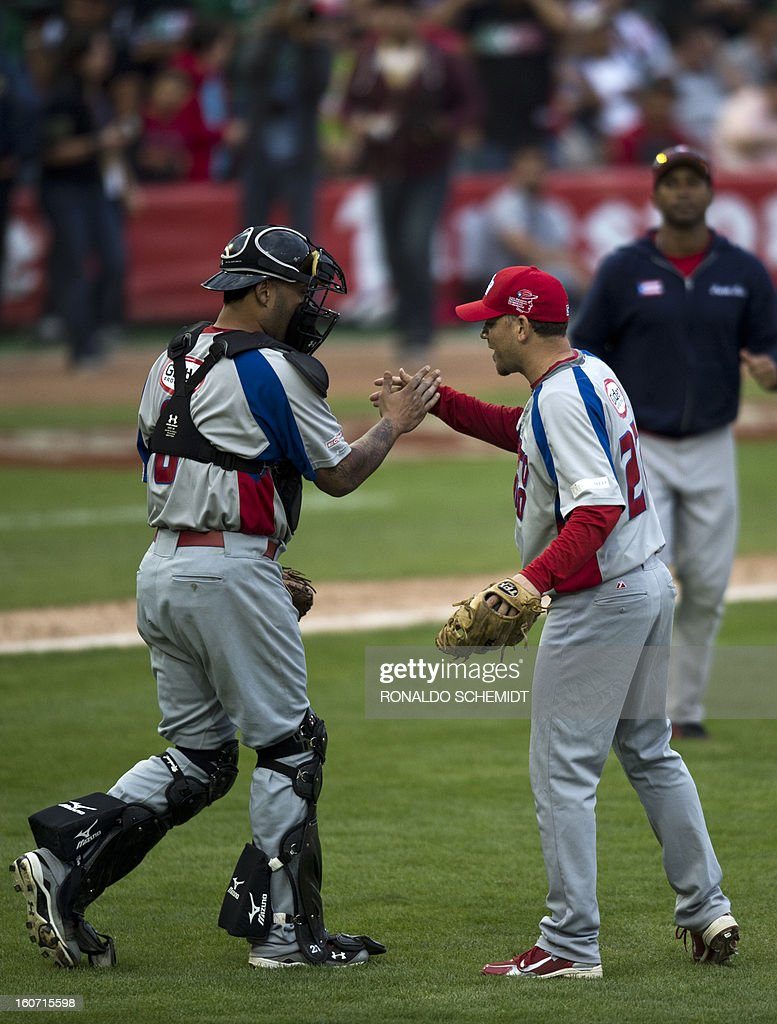 Pitcher Saul Rivera (R) of Criollos de Caguas of Puerto Rico, celebrates with catcher Ramon Castro their victory against Leones del Escogido of Dominican Republic, during the 2013 Caribbean baseball series, on February 4, 2013, in Hermosillo, Sonora State, in the northern of Mexico. AFP PHOTO/Ronaldo Schemidt