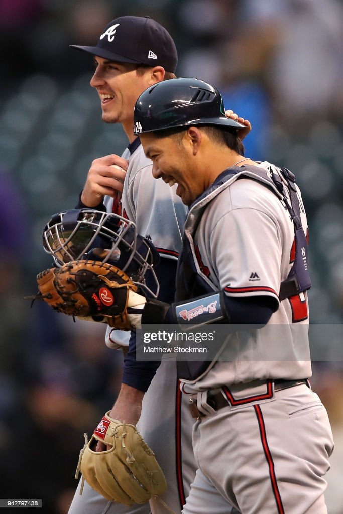 Pitcher Shane Carle #51 of the Atlanta Braves and catcher Kurt Suzuki #24 celebrate their win over the Colorado Rockies at Coors Field on April 6, 2018 in Denver, Colorado.
