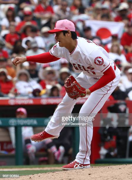 Pitcher Shohei Ohtani of the Los Angeles Angels of Anaheim pitches in the seventh inning as a fan holds up a Japanese flag in the stands during the...