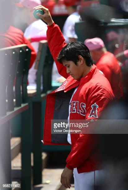 Pitcher Shohei Ohtani of the Los Angeles Angels of Anaheim stretches and stays loose in the middle of the first inning during the MLB game against...