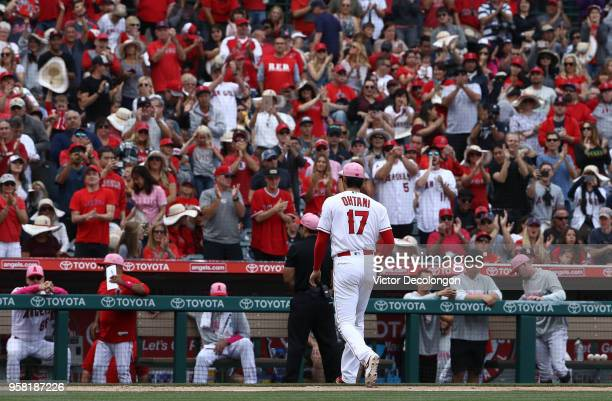 Pitcher Shohei Ohtani of the Los Angeles Angels of Anaheim walks to the dugout after being taken out of the game in the seventh inning during the MLB...
