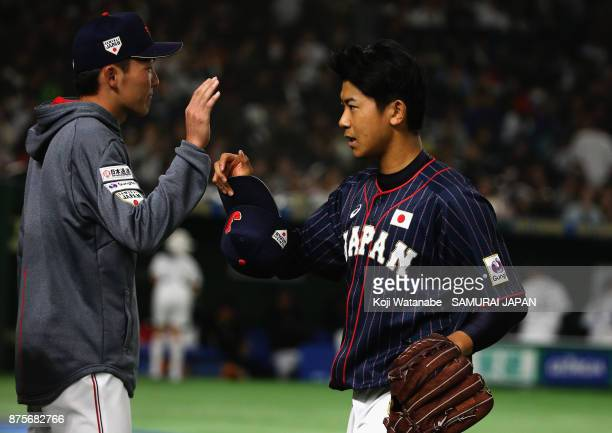Pitcher Shota Imanaga of Japan high fives with his team mate Infielder Sosuke Genda after the bottom of sixth inning during the Eneos Asia...