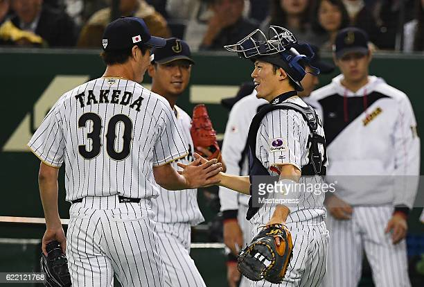 Pitcher Shota Takeda is congratulated by catcher Shota Ohno of Japan after the first inning during the international friendly match between Japan and...