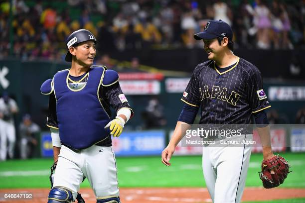 Pitcher Tomoyuki Sugano and Catcher Seiji Kobayashi of Japan talk while walking to the dugout after the bottom of the third inning during the SAMURAI...