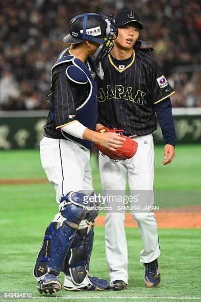 Pitcher Toshiya Okada of Japan is congratulated by Catcher Seiji Kobayashi after the bottom of the fifth inning the World Baseball Classic Pool B...
