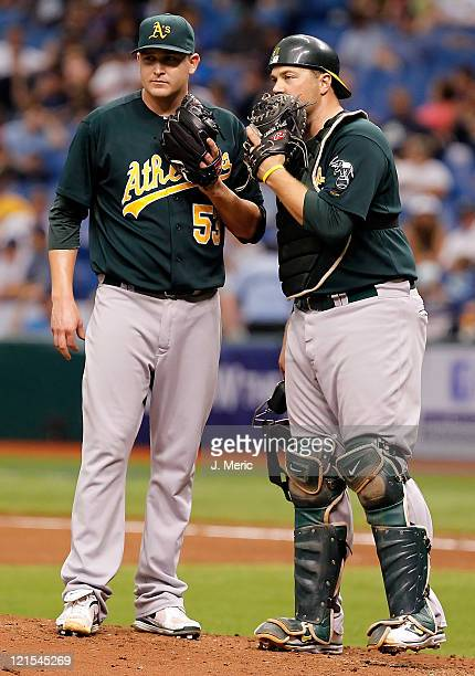 Pitcher Trevor Cahill of the Oakland Athletics talks to catcher Landon Powell against the Tampa Bay Rays during the game at Tropicana Field on August...