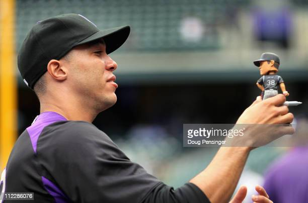 Pitcher Ubaldo Jimenez of the Colorado Rockies signs his bobble head for a fan prior to the game on autograph day as the Rockies host the Chicago...