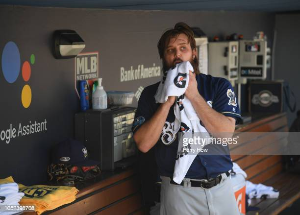 Pitcher Wade Miley of the Milwaukee Brewers wipes himself down in the dugout after leaving the game after facing just one batter during the first...