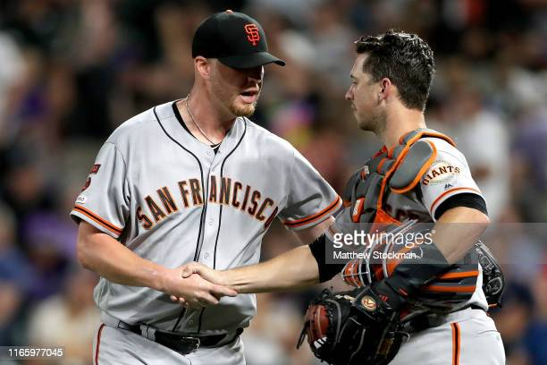 Pitcher Will Smith and catcher Buster Posey of the San Francisco Giants celebrate the last out in the ninth inning against the Colorado Rockies at...