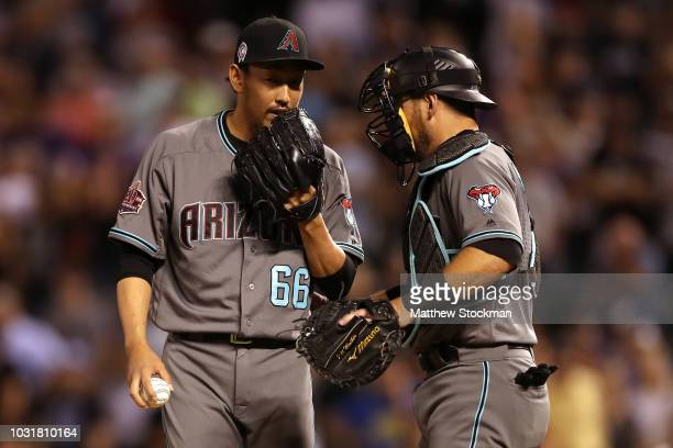 Pitcher Yoshihisa Hirano of the Arizona Diamondbacks confers with catcher Jeff Mathis in the ninth inning against the Colorado Rockies at Coors Field...
