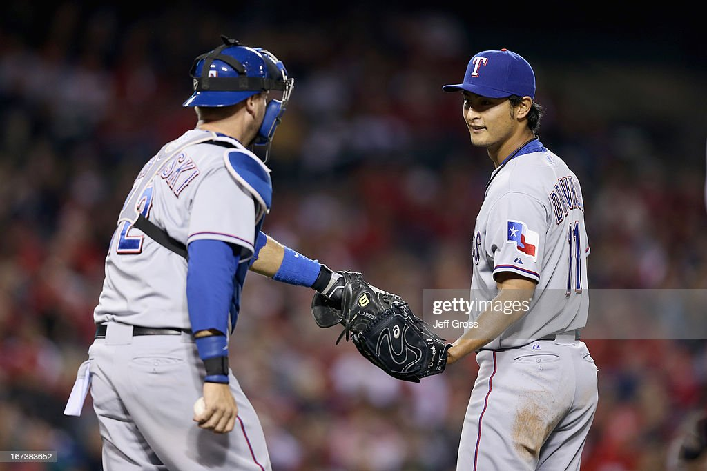 Pitcher Yu Darvish #11 and catcher A.J. Pierzynski #12 of the Texas Rangers talk in the fourth inning against the Los Angeles Angels of Anaheim at Angel Stadium of Anaheim on April 24, 2013 in Anaheim, California.