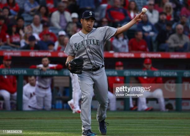 Pitcher Yusei Kikuchi of the Seattle Mariners fields a throw to first base for the third out in the first inning of the MLB game against the Los...