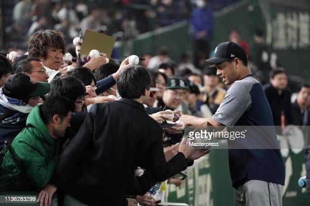 Pitcher Yusei Kikuchi of the Seattle Mariners signs autographs for fans prior to the game between the Yomiuri Giants and Seattle Mariners at Tokyo...