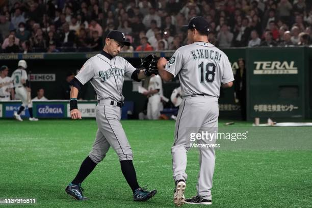 Pitcher Yusei Kikuchi of the Seattle Mariners welcomes Outfielder Ichiro Suzuki after the 4th inning during the game between Seattle Mariners and...