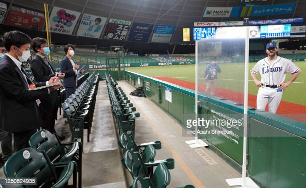 Pitcher Zach Neal of the Saitama Seibu Lions is interviewed through the transparent plastic sheet to avoid possible Covid19 infections after the game...