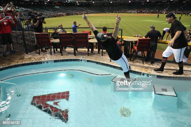 Pitcher Zack Godley of the Arizona Diamondbacks falls into the outfield pool after defeating the Miami Marlins and clinching a post season birth...
