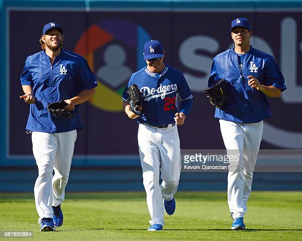 Pitchers Clayton Kershaw Scott Kazmir and Rich Hill of the Los Angeles Dodgers jog during batting practice prior to the start of the baseball game...