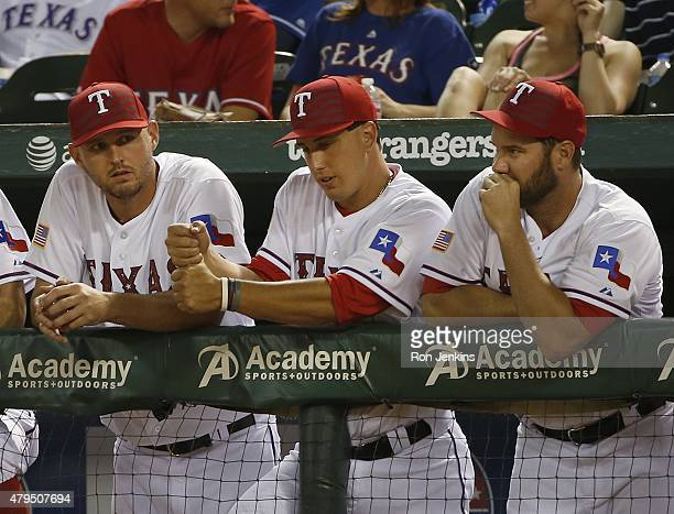 Pitchers Matt Harrison Derek Holland and Colby Lewis of the Texas Rangers look on from the dugout during the game against the Los Angeles Angels of...