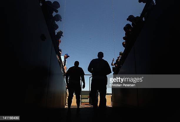 Pitchers Mitch Lively and Andrew Kown of the San Francisco Giants walk out to the field past fans before the spring training game against the Kansas...