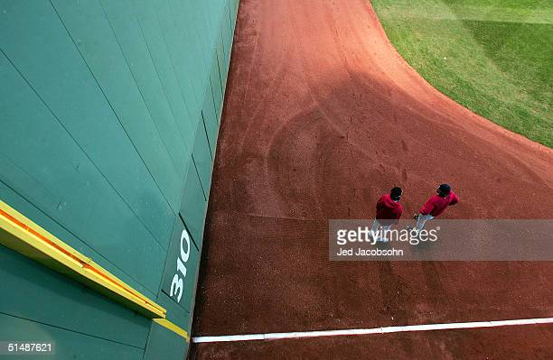 """Pitchers Pedro Martinez and Derek Lowe of the Boston Red Sox warm-up near the """"Green Monster"""" before game three of the American League Championship..."""