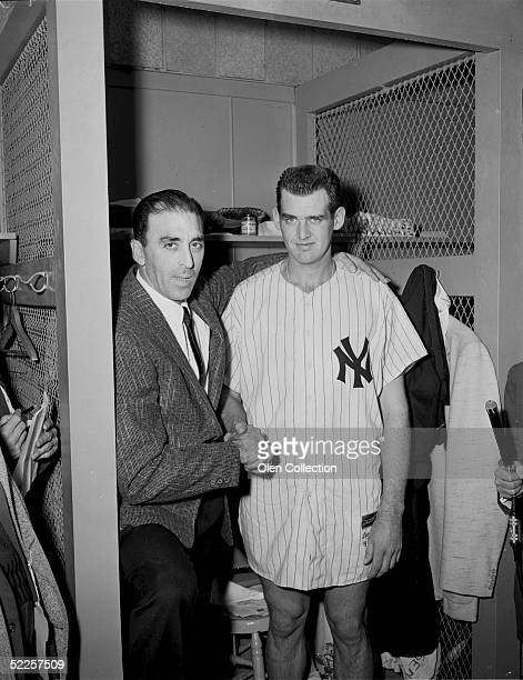 Pitchers Sal Maglie of the Brooklyn Dodgers and Don Larsen of the New York Yankees meet again in the clubhouse at Yankee Stadium after Larsen pitched...