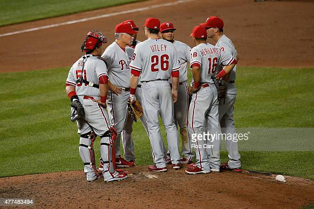Pitching coach Bob McClure talks with Chase Utley and Jeff Francoeur of the Philadelphia Phillies who came on in relief to pitch to the Baltimore...