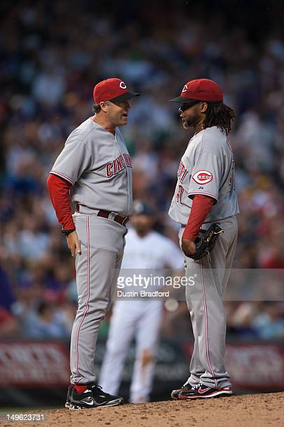 Pitching coach Bryan Price as a word with Johnny Cueto of the Cincinnati Reds during the sixth inning of a game against the Colorado Rockies at Coors...