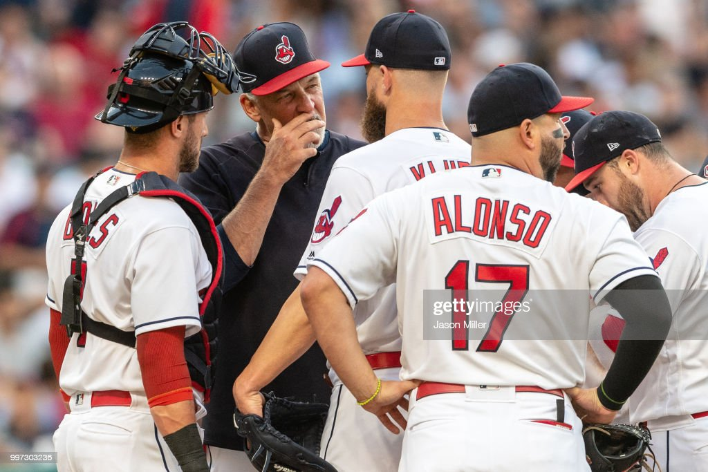 Pitching coach Carl Willis #51 of the Cleveland Indians comes to the mound to talk with starting pitcher Corey Kluber #28 and catcher Yan Gomes #7 during the fourth inning against the New York Yankees at Progressive Field on July 12, 2018 in Cleveland, Ohio.