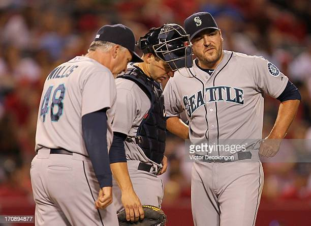 Pitching coach Carl Willis of the Seattle Mariners walks to the mound to have a word with catcher Mike Zunino and pitcher Joe Saunders in the eighth...