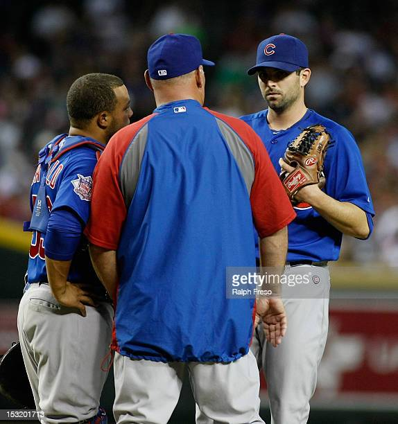 Pitching coach Chris Bosio of the Chicago Cubs makes a visit to the mound to talk with pitcher Justin Germano and catcher Wellinton Castillo during a...