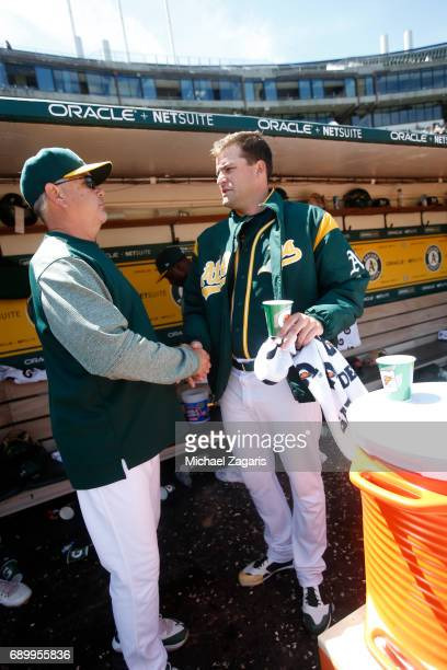 Pitching Coach Curt Young of the Oakland Athletics congratulates Andrew Triggs in the dugout during the game against the Los Angeles Angels of...