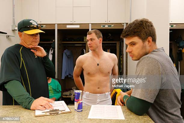 Pitching Coach Curt Young of the Oakland Athletics goes over hitters in the clubhouse with Sonny Gray and Josh Phegley prior to the game against the...