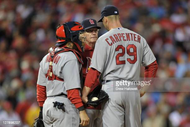 Pitching coach Dave Duncan of the St Louis Cardinals visits with Chris Carpenter and Yadier Molina in the first inning against the Philadelphia...